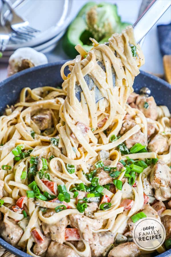 Tongs lifting Cajun Chicken Pasta to show off the creamy sauce