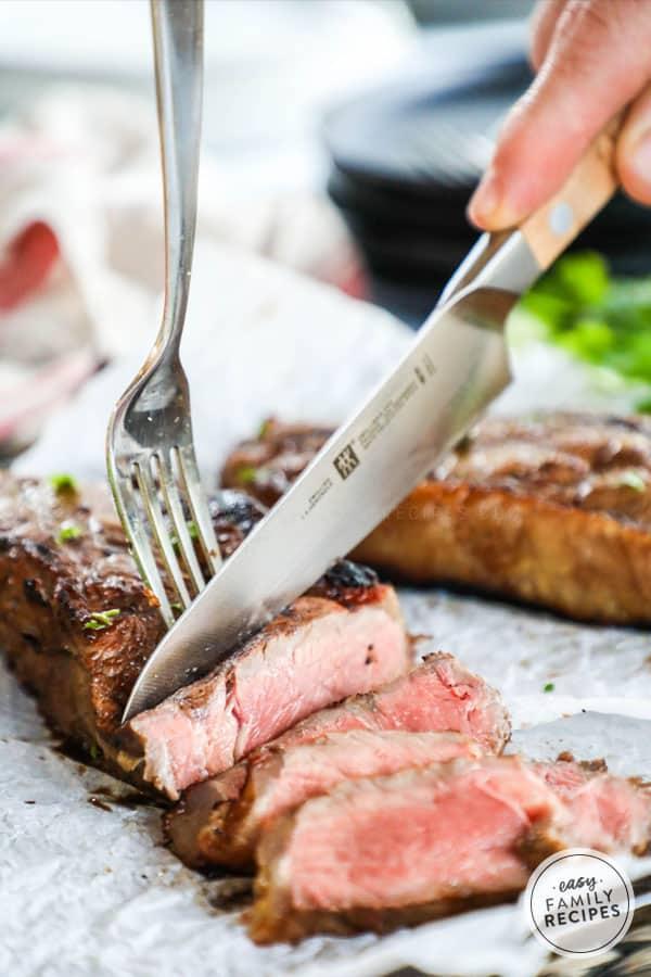 Knife cutting into tender strip steak