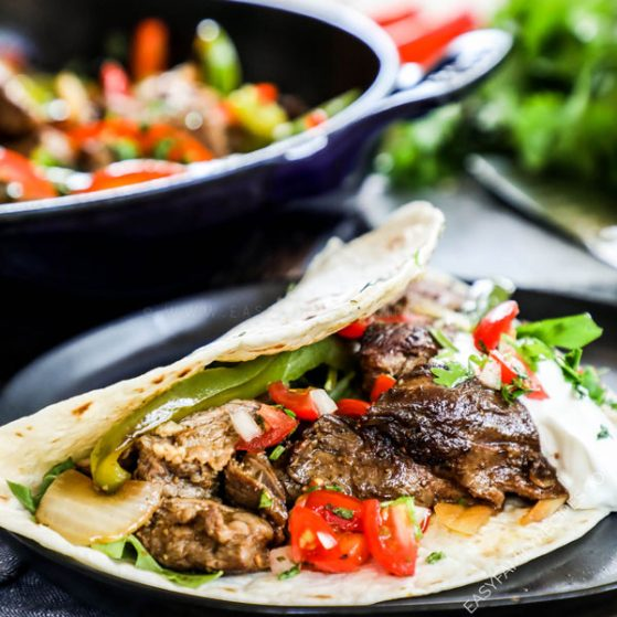 Steak Fajitas Recipe placed in a tortilla and topped with pico de gallo and sour cream