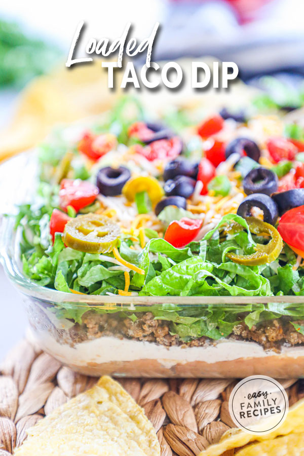 Taco dip from the side so you can see layers of beans, meat, cream cheese, sour cream, lettuce and tomatoes