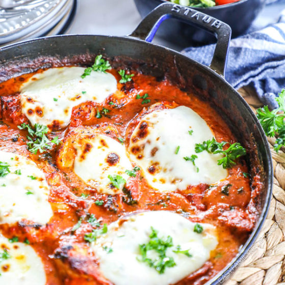Mozzarella topped Chicken in a creamy tomato sauce shown in a skillet