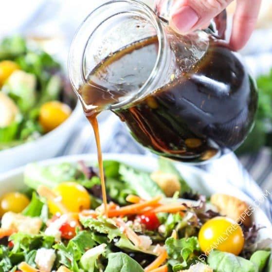 Pouring Homemade Balsamic Vinaigrette over a salad
