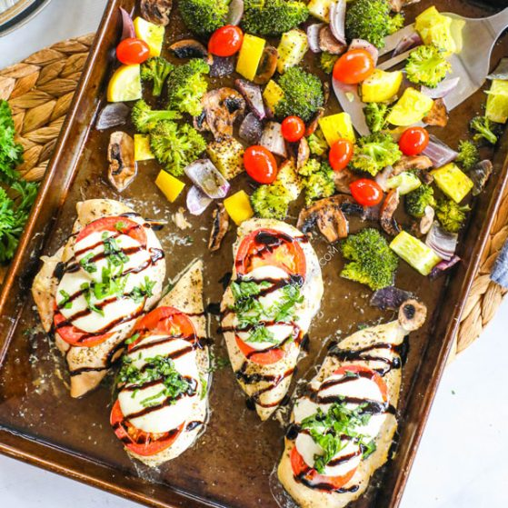 Chicken breast topped with tomato, mozzarella, and basil cooked on a sheet pan with veggies