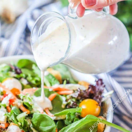 Homemade Creamy Italian Salad Dressing being poured onto a salad
