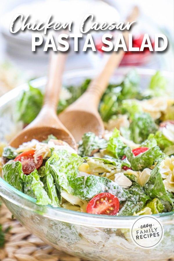 Chicken Caesar Pasta Salad in a glass bowl with wooden serving spoons