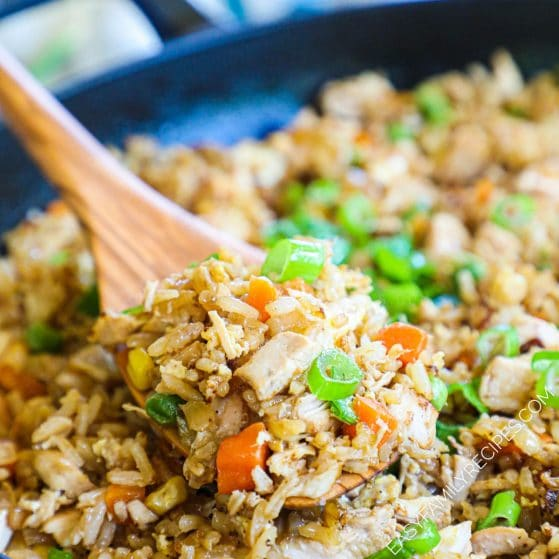 Skillet full of easy Chicken fried rice with a spoon in it.