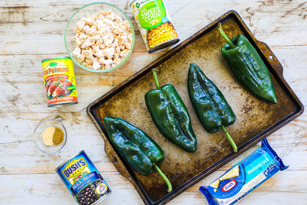 Ingredients for chicken stuffed poblano peppers, including rotisserie chicken, corn, black beans, enchilada sauce, cheese and poblano peppers