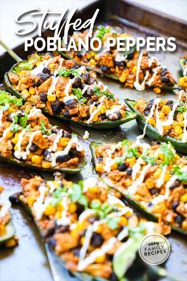Poblano Peppers stuffed with chicken and drizzled with sour cream on a baking sheet