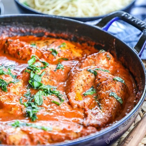 Chicken in tomato basil sauce simmering in a skillet