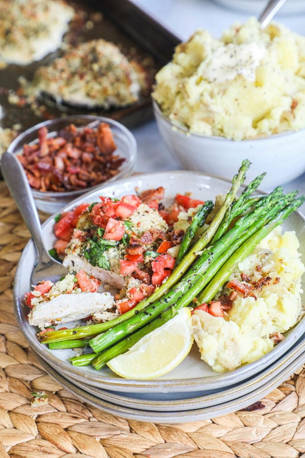 Bruschetta Chicken with mozzarella crust plated with bacon mashed potatoes and roasted asparagus