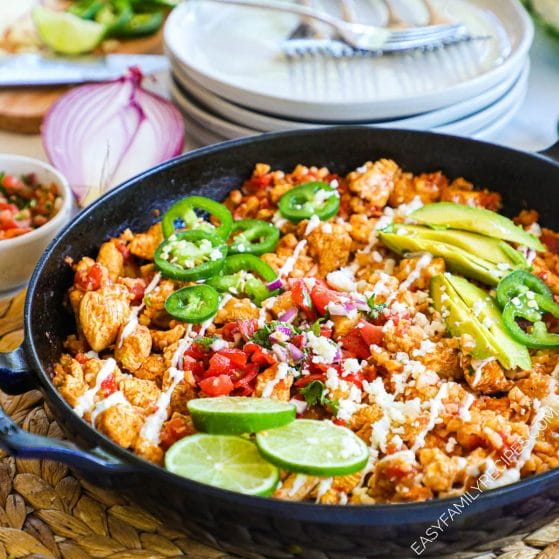 Chicken and Cauliflower rice burrito bowl in pan topped with avocado, lime and pico de gallo