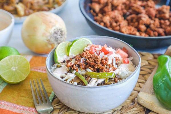 Tex Mex Pork Enchilada Bowl topped with slsa mexicana and spiced crema