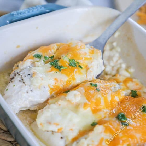 Lifting chicken breast with cheese topping out of casserole dish