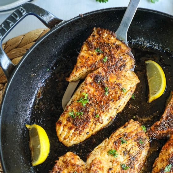 Blackened fish cooked in a cast iron skillet and garnished with lemon wedges and parsley