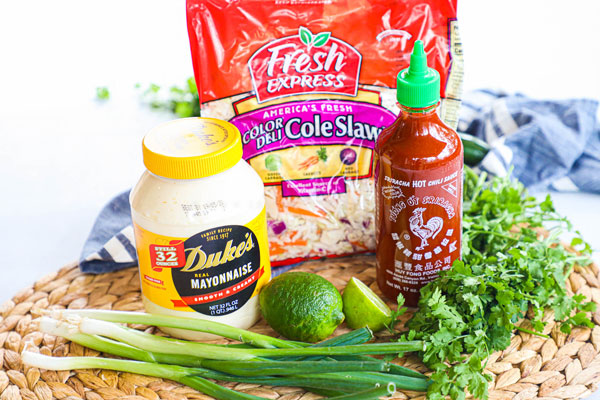 Ingredients for spicy asian coleslaw including cabbage or coleslaw mix, mayonnaise, lime juice, sriracha, green onions, cilantro
