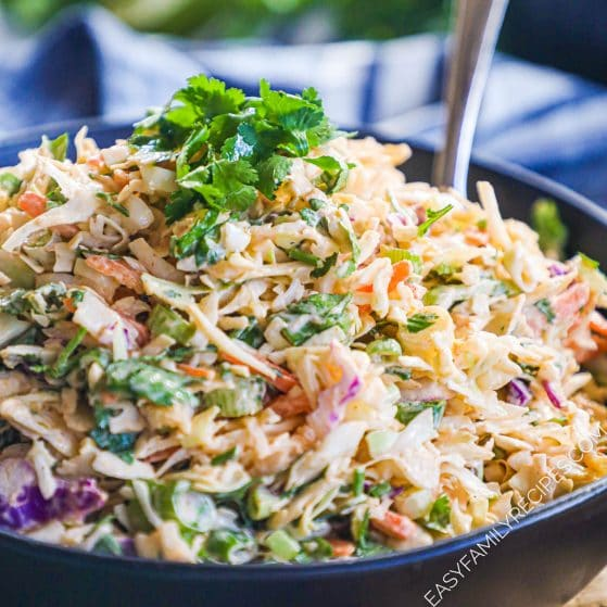 Bowl of homemade asian coleslaw with sriracha and lime and garnished with cilantro