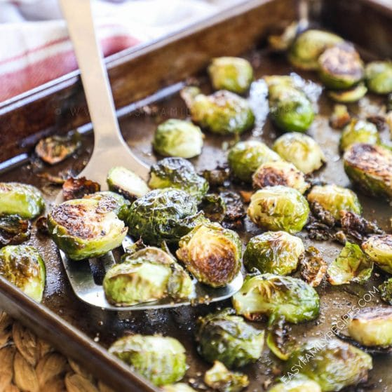 Oven Brussels Sprouts slightly charred being lifted with a spatula