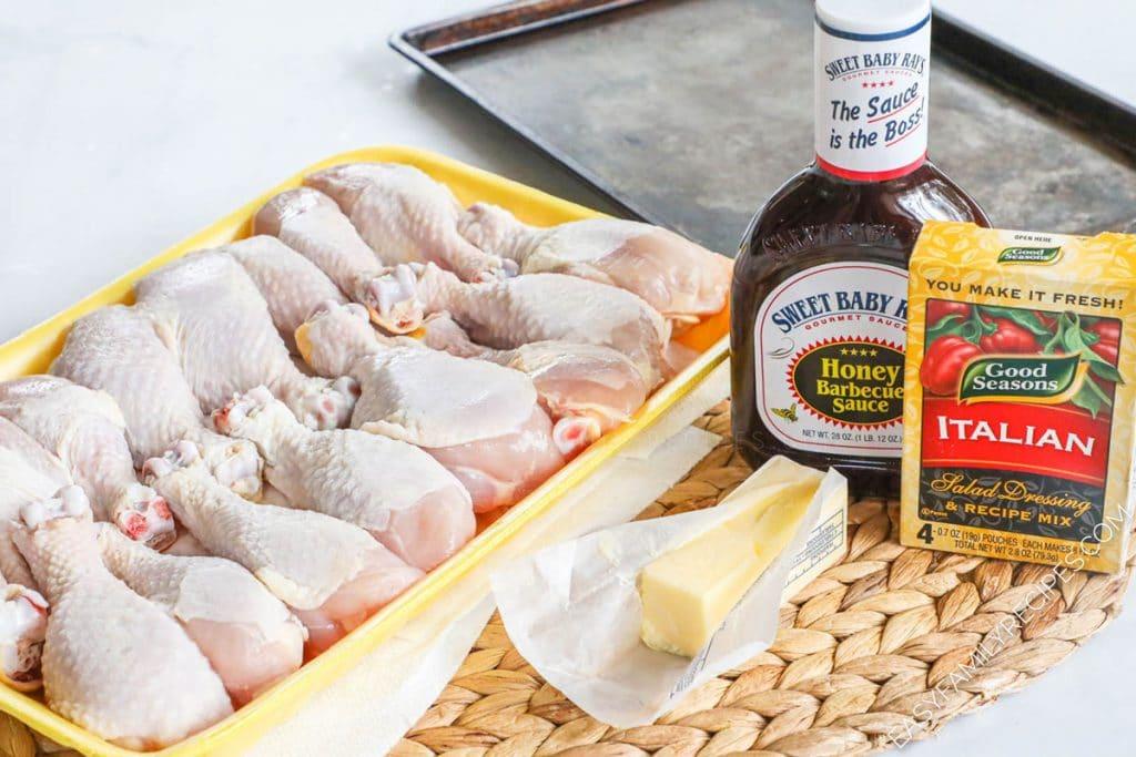 Ingredients for making baked chicken drumsticks including chicken legs, bbq sauce, butter, italian seasoning
