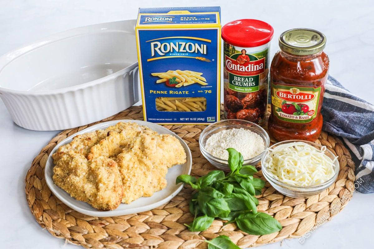 Chicken Parmesan Casserole Ingredients including pasta, breaded chicken, parmesan, marinara sauce, bread crumbs, mozzarella and basil