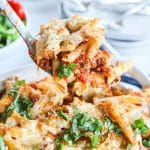 Big spoonful of chicken parmesan casserole with noodles, chicken and pasta sauce covered in cheese and garnished with fresh basil being scooped from casserole dish